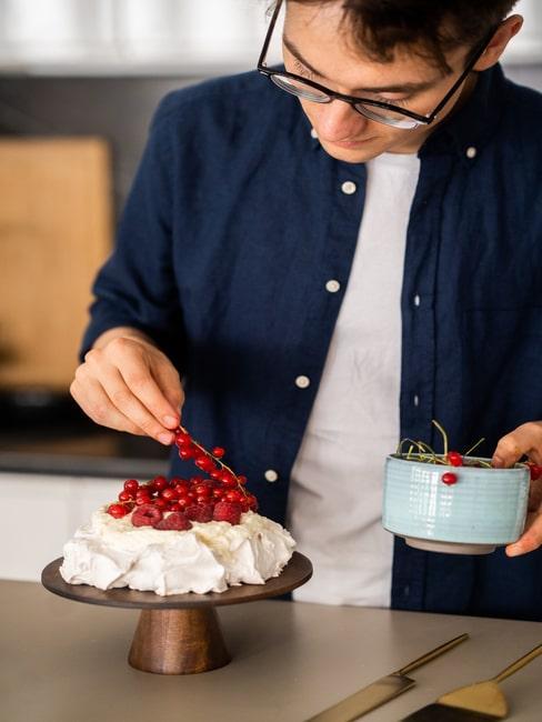 Kucharz dekorujacy tort Pavlova porzeczkami