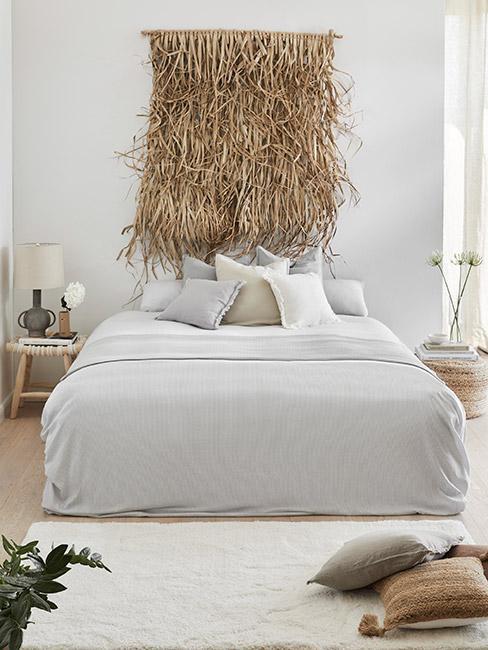 sypialnia z popialatym łóżkiem z dekoracją ścienną z trawy morskiej w tle