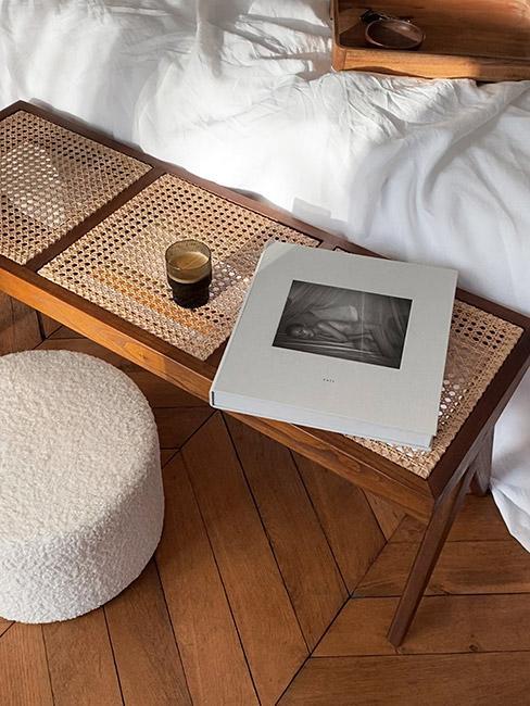 ławka z plecionki wiedeńskiej przy łóżku z białą narzutą obok pufy boucle