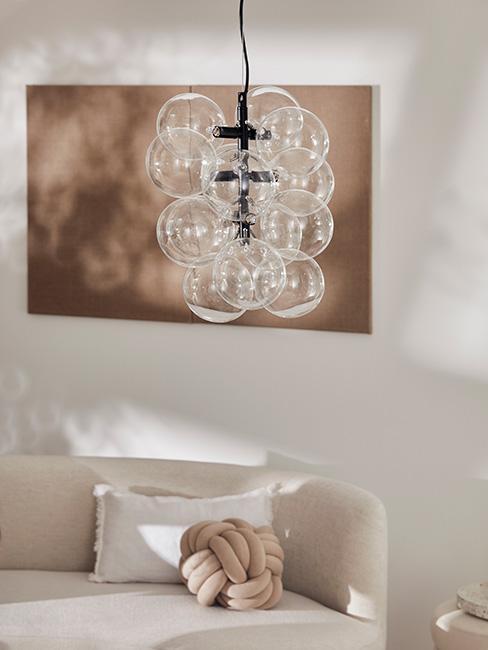 lampa w kształcie bącelków na tle beżowej ściany