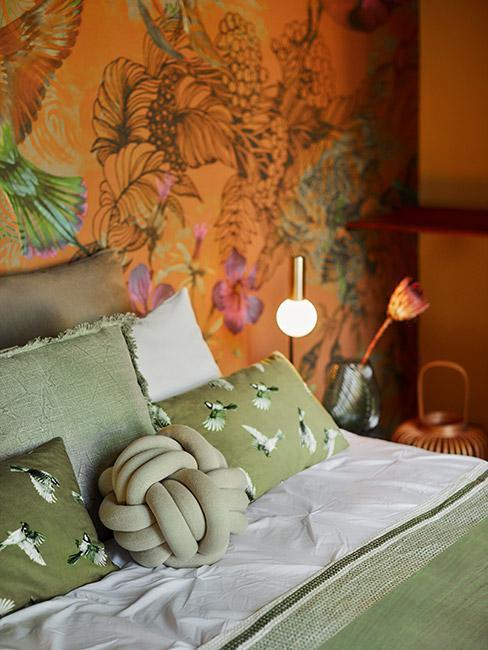 sypialnia z kolorową tropikalną tapetą w jolorze pomarańczowym obok łóżka z zielonymi poduszkami