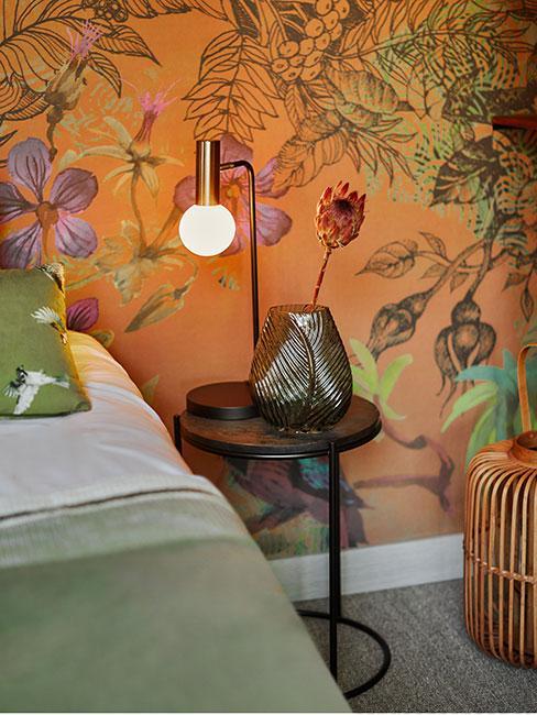 sypialnia z pomarańczową tapetą w kwiaty i zieloną narzutą
