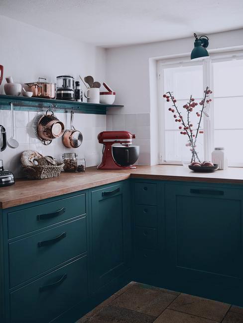 ciemna kuchnia z ciemnozielonymi szafkami na tle białej ściany