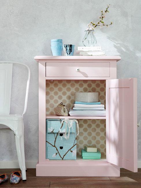różowa pastelowa komoda obok białego krzesła