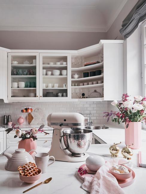 Kuchnia w stylu prowansalskim z białymi szafkami, różowymi dodatkami i kwiatami