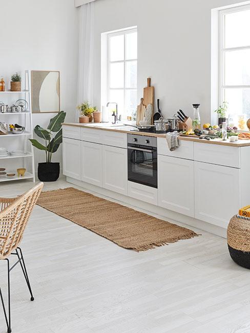 Jasna kuchnia z drewnianym blatem, jasną białą podłogą i dodatkami w kolorze ciemnego beżu