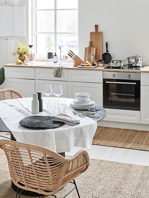Kuchnia z drewnianym blatem, dodatkami z drewna i stołem przykrytym białym obrusem