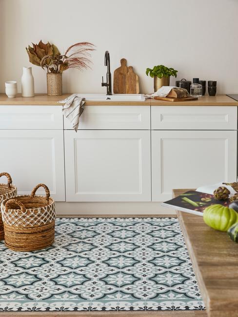 Biała kuchnia z drewnianym blatem, podłogą drewniana połączoną z płytkami w niebieski wzór