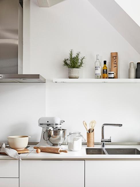 kuchnia w jasnych barwach, z drewnianymi dodatkami i kwiatem na półce