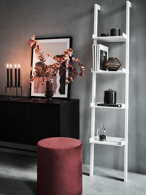 czarna komoda na tle szarej ściany obok białego regału typu drabina, na której stoji wazon z jesiennymi liśćmi