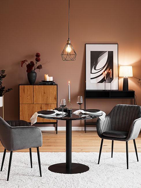 jesienna jadalnia ze ścianą ciepłym kolorze terakoty i czarnym okrągłym stołem