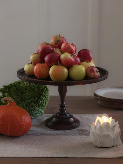 jabłka na czarnej etażerce w kuchni obok dyni i kapusty