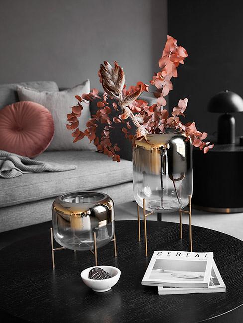 pozłacane szklane wazony z jesiennymi liśćmi na czarnym stoliku kawowym na tle szarej sofy
