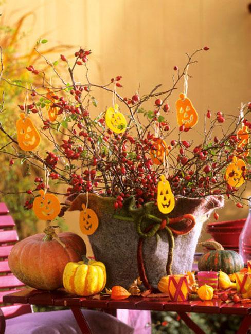 gałązki głogu w doniczce z filcu w ogrodzie ozdobione filcowymi dekoracjami w kształcie dyni