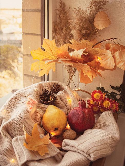 gruszka i granat na wełnianym pledzie na oknie obok jesiennych liści
