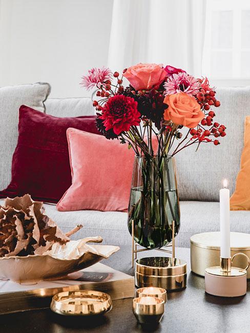 świeże kwiaty w jesiennych kolorach w szklanym zielonym wazonie na czarnym stoliku kawowym na tle szarej sofy z poduszkami w kolorach jesieni