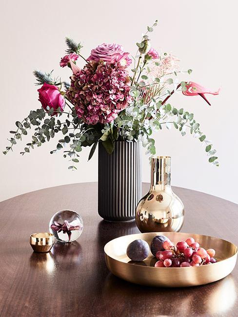 szary wazon z jesiennymi kwiatami na okrągłym stole obok złotej tacy z owocami