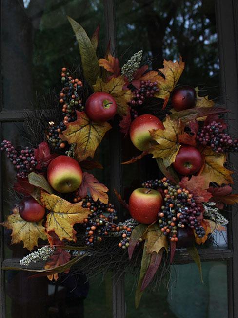 jesienny wieniec z suszonych liści i jabłek na ciemnych drzwiach