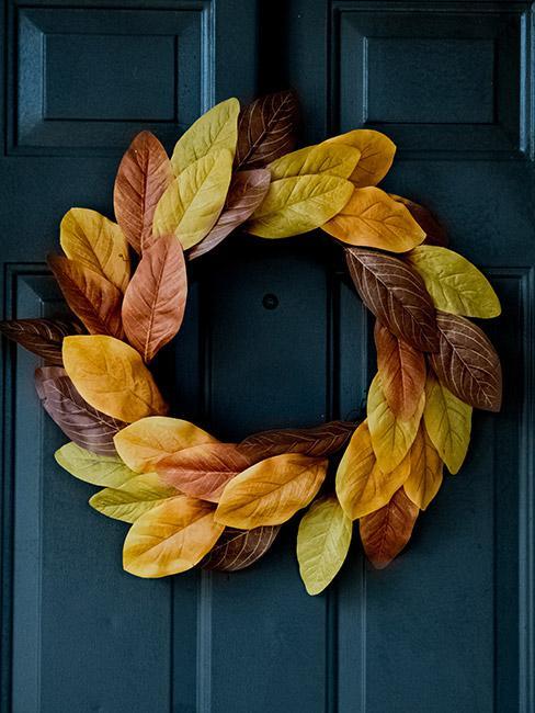 wieniec z żółtych liści na ciemnoniebieskich drzwiach