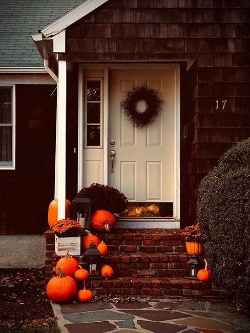 pomarańczowe dynie jako dekoracja ganku z białymi drzwiami