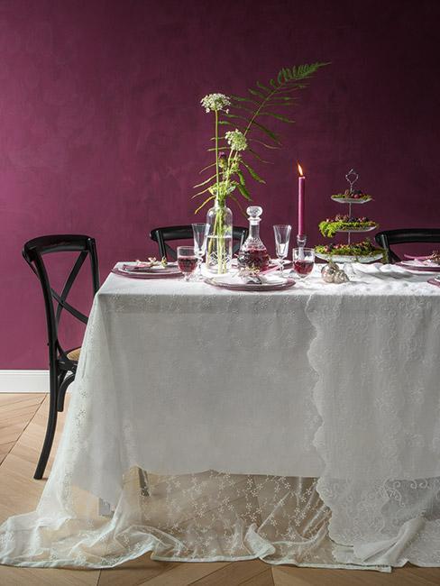 stół z białym obrusem i ciemnymi drewnianymi krzesłami na tle burgundowej ściany