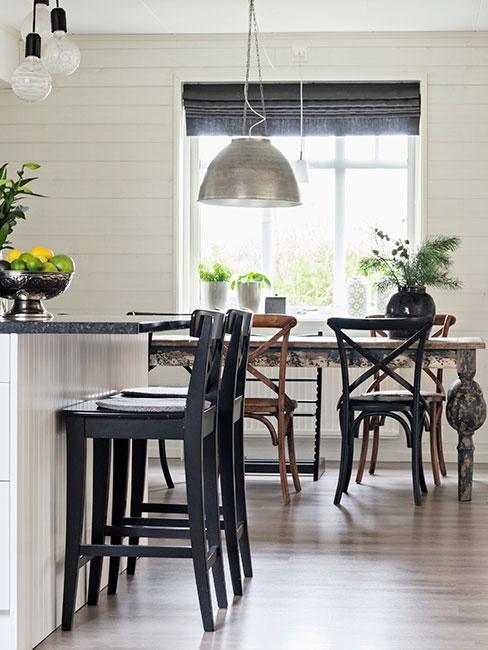 Biało-czarna kuchnia w stylu francuskim: czarne krzesła, blaty i rolety, białe szafki