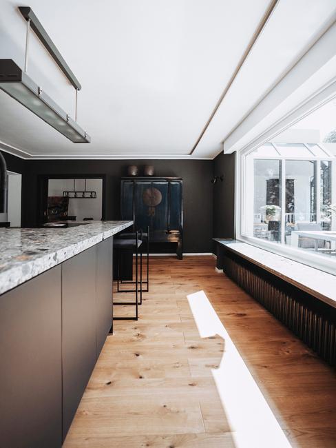 Przestrzenna kuchnia w kolorze czarnym i białym, z marmurowymi blatami i białymi ramami okiennymi na całej ścianie