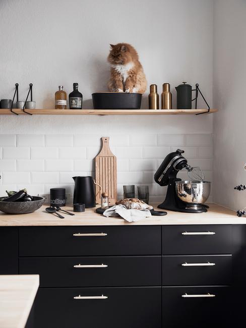 Czarne szafki z drewnianym blatem, drewnianymi i czarnymi dodatkami z kotem siedzącym na półce