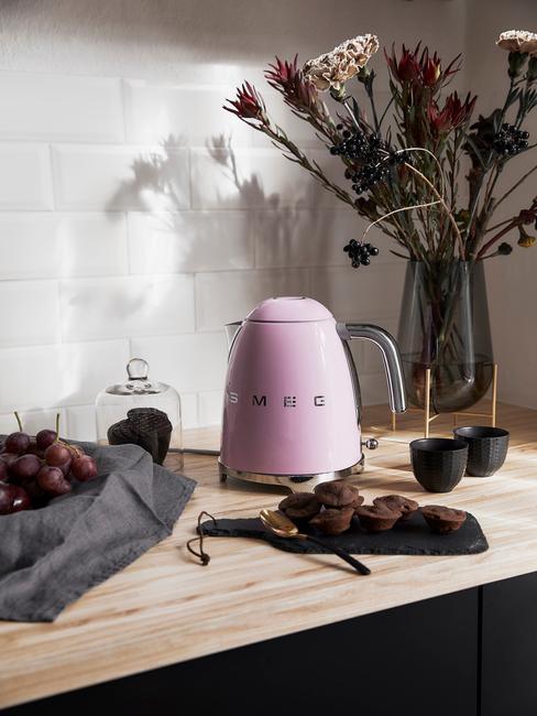 Różowy czajnik marki Smeg w biało czarnej kuchni z białymi ścianami, czarnymi szafkami i drewnianym blatem
