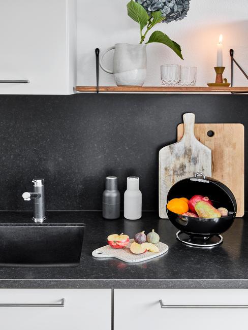 Czarna ściana w biało-czarnej kuchni, ciemne blaty, białe szafki i drewniane dodatki
