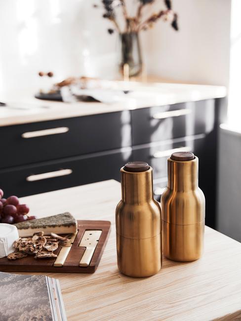 złote butelki na drewnianym blacie w biało-czarnej kuchni