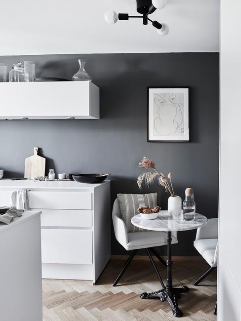 Czarna ściana w biało-czarnej kuchni, z białymi meblami stołem i krzesłami