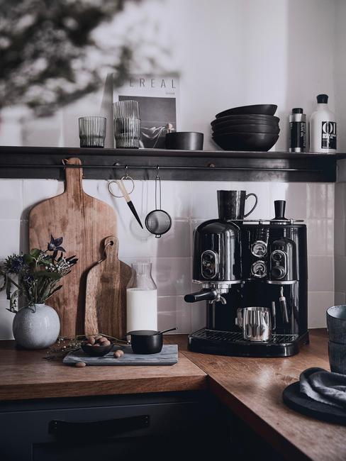 Dodatki w kolorze czerni i drewniane deski na drewnianym blacie na tle białej ściany w kuchni