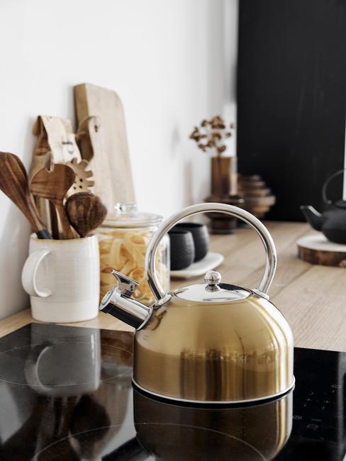 złoty czajnik na drewnianym blacie w biało czarnejkuchni