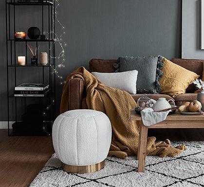 Salon z drewnianą podłogą, grafitową ścianą, jasnym dywanem z dodatkami w ciepłych odcieniach