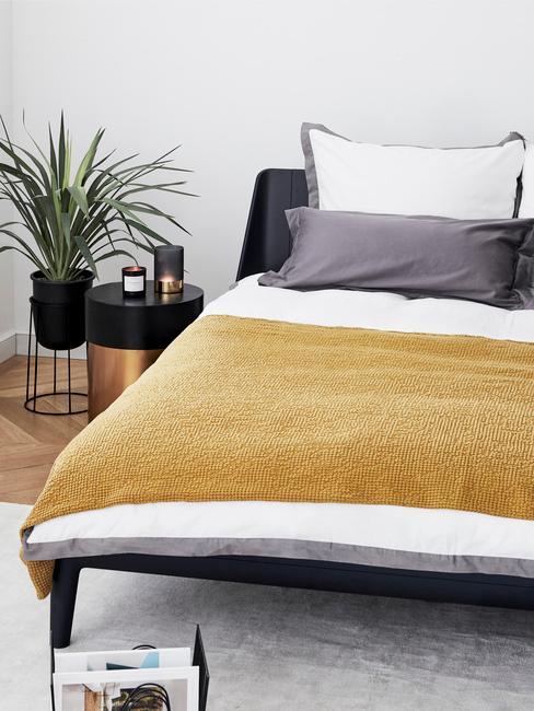 łóżko z białą pościelą, musztardowym pledem, grafitowymi poduszkami i czarnymi dodatkami