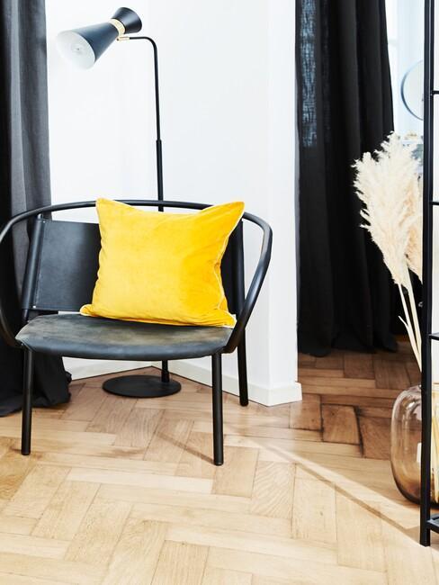 Fotel na drewnianej podłodze w kolorze grafitowym z akcentem kolorystycznym w postaci żółtej poduszki