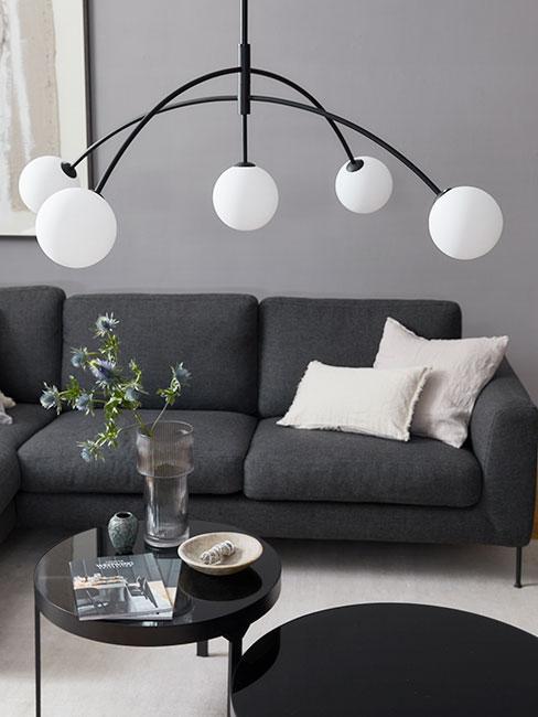 kolor grafitowy: kanapa w kolorze grafitowym, poduszki w jasnym odcieniu, czarne dodatki i lampa z białym kloszem