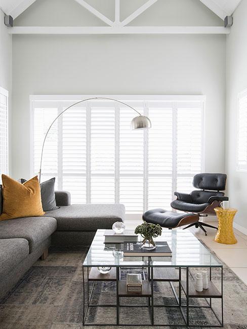 Jasne pomieszczenie z kanapą w kolorze grafitowym, szklany stół i żółte dodatki
