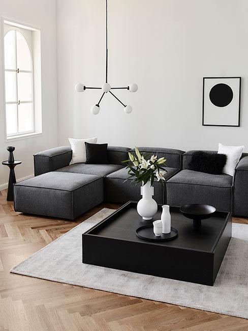 kolor grafitowy: pokój z jasnymi ścianami, drewnianą podłogą, jasnym dywanem i czarnym stolikiem i kanapą w kolorze grafitowym