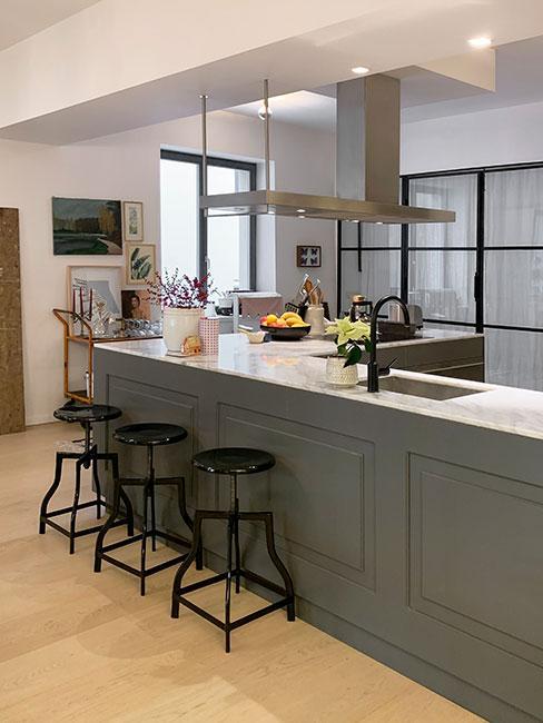 kolor grafitowy: kuchenna wyspa w kolorze grafitowym, ciemne krzesła, drewniana podłoga i jasne ściany