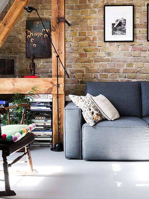 kolor grafitowy: sofa w kolorze grafitowym na tle ściany wyłożonej cegłami, obok regał z drewna