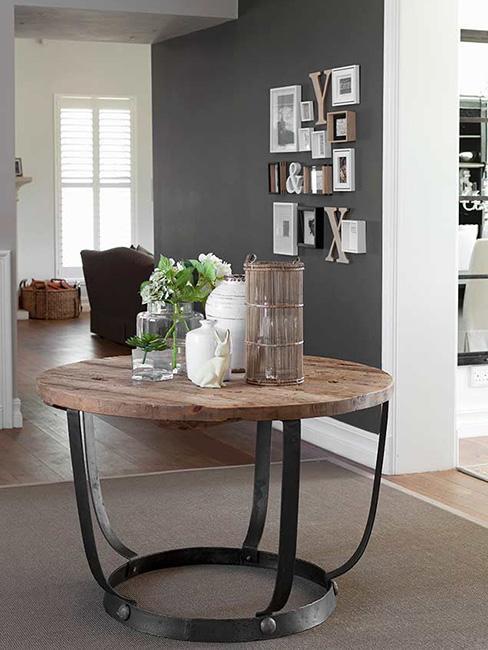 Grafitowa ściana w jadalni na której wiszą zdjęcia w białych i czarnych ramkach, na pierwszym planie stół z metalowymi nogami i drewnianym blatem na którym stoją białe i beżowe dodatki