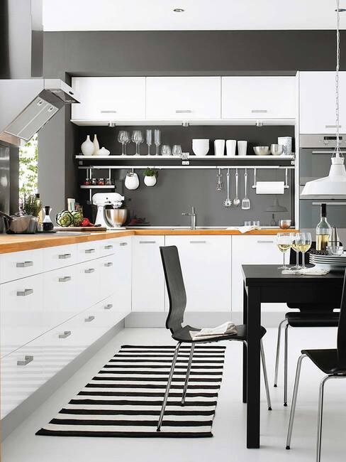 Kuchnia z białymi szafkami, drewnianą podłogą czarno-białym dywanem i czarnymi dodatkami