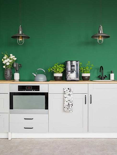 Zielona ściana w kuchni z jasnymi szafkami