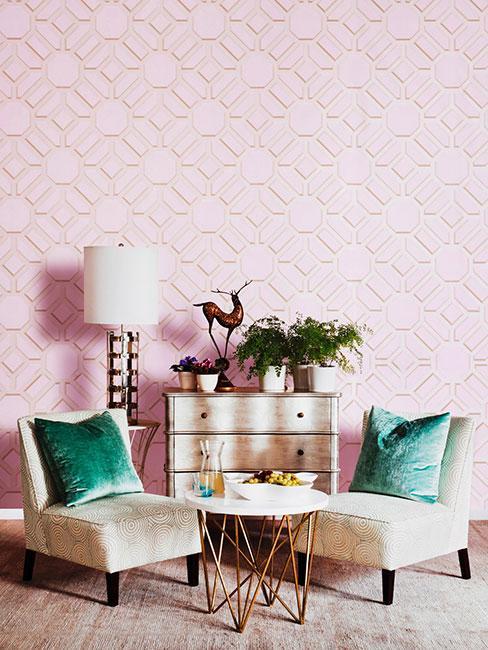 Różowa ściana z fotelami i zielonymi poduszkami