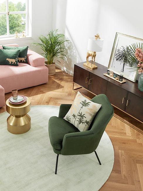 salon z różową sofą i zielonym fotem oraz tropikalnymi dekoracjami