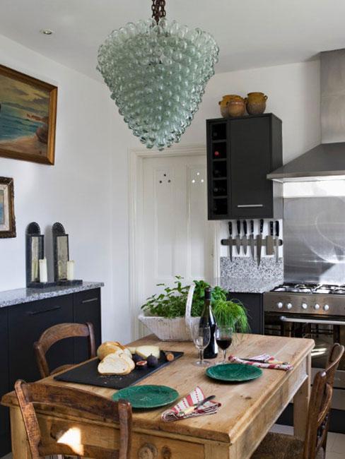 rustykalna kuchnia z lampą z zielonego szkła i drewnianym stołem i zastawą w zieleni