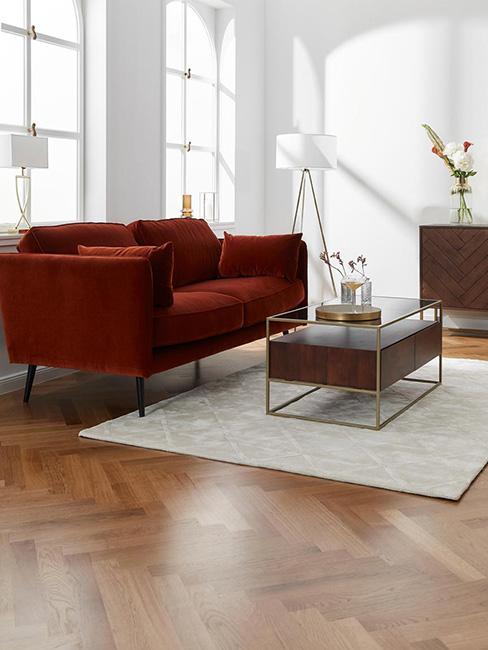 salon z ciemnoczerwoną sofą obok stolika drewnianyego ze złotymi akcentami