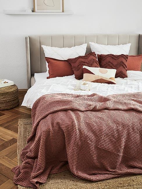 Sypialnia z poduszkami i narzutą w kolorze terakoty w stylu boho